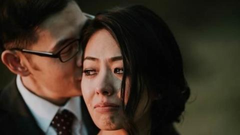 Er flüstert ihr etwas ins Ohr. Dann bricht sie in Tränen aus