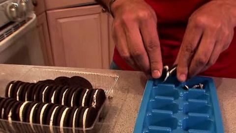 Er tut Oreo Stücke in eine Eiswürfelform. Was er danach macht, ist einfach genial!
