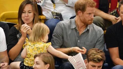 Ein kleines Mädchen stibitzt das Popcorn von Prinz Harry. Seine Reaktion ist herrlich