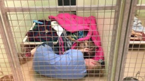 Sie findet eine Helferin in einem Käfig liegend und beginnt zu weinen