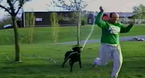 Der Hund versucht das Herrchen nass zu machen