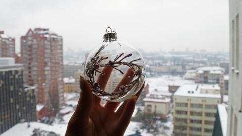 Sie nimmt eine Weihnachtskugel und macht damit etwas Geniales