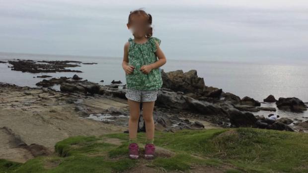Ein Vater fotografiert seine Tochter am Strand... Auf dem Foto sieht er hinter ihr gespenstische Beine!