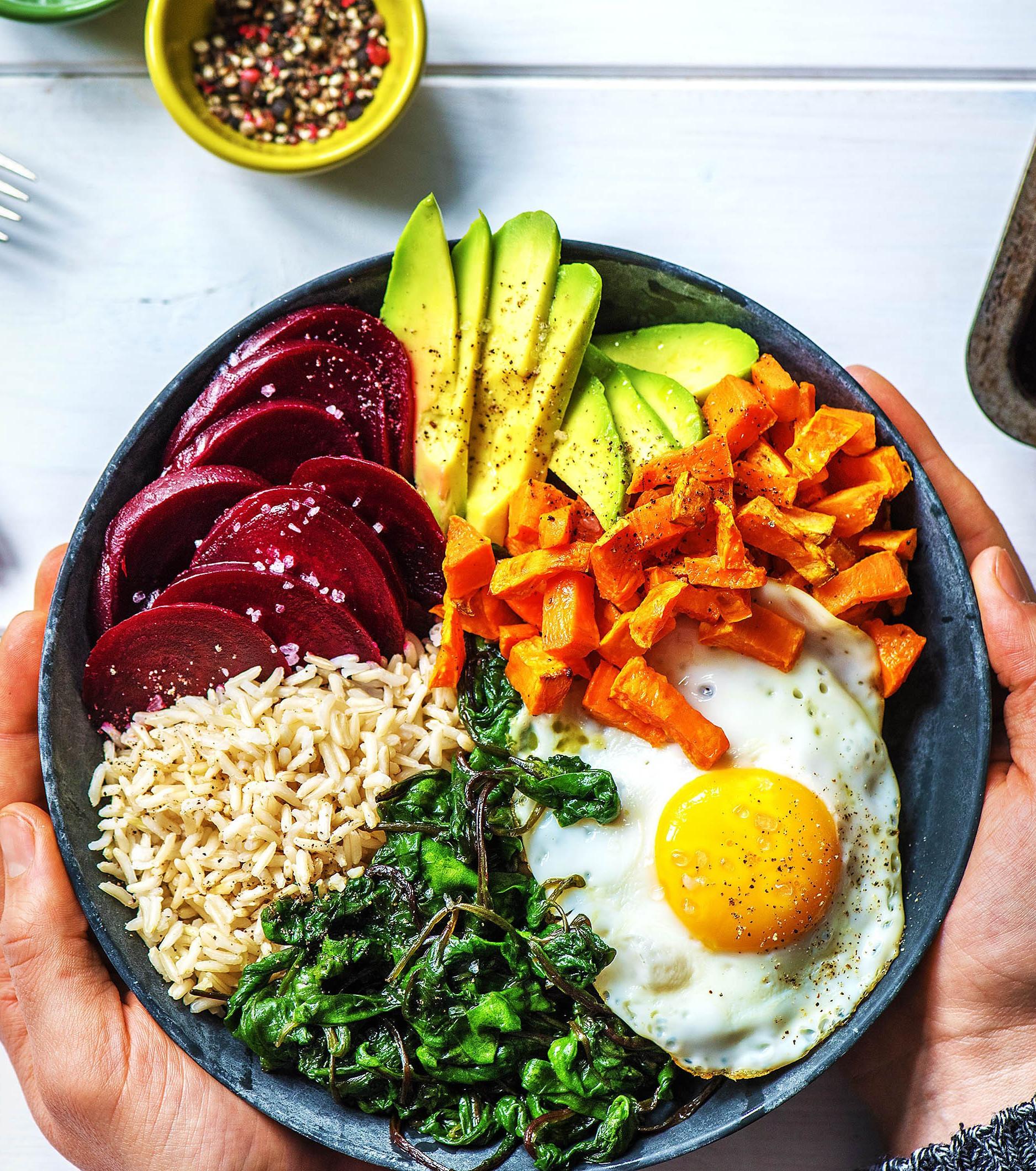 Buddha Bowl mit Rote Bete, Avocado, Reis, Süßkartoffeln und Spiegelei