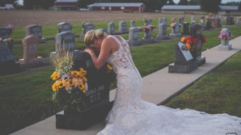 Herzzerreißend: Braut kniet am Tag ihrer Hochzeit vor einem Grabstein